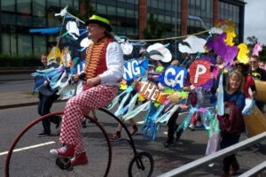 Bridging the Gap supporters taking part in a street parade and led by man on penny farthing style old bike
