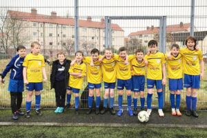 Primary school kids from Broomhill Sports Club lined up in football kit with arms round each other