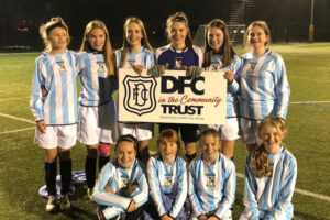 Teen girls posing in football kit on a pitch and holding up Dundee FC in the Community Trust logo on a board