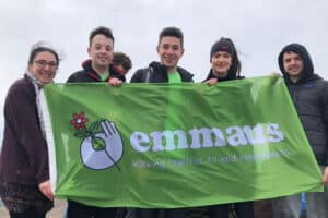 Volunteers and workers from Emmaus Glasgow holding big green flag with the Emmaus logo on it in white