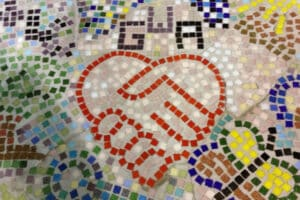 Colourful mosaic with two hands clasped in heart shape with GWA for Glasgow Women's Aid above