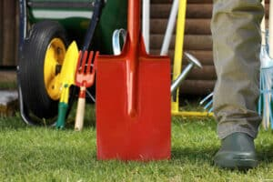 Person with shiny red spade and gardening tools