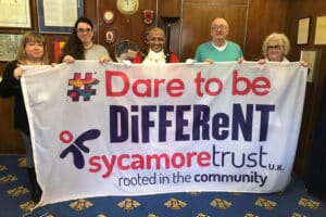 Local mayor and volunteers golding up large banner featuring dare to be different and the Sycamore Trust logo