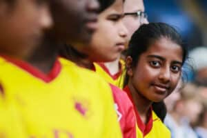 Young girl standing in a row ahead of a football match in Watford kit and peering down the line at the camera